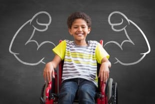 Boy in wheelchair in front of chalk board with powerful arms drawn in