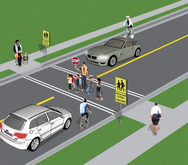 Image of students crossing with a crossing guard at a crossover