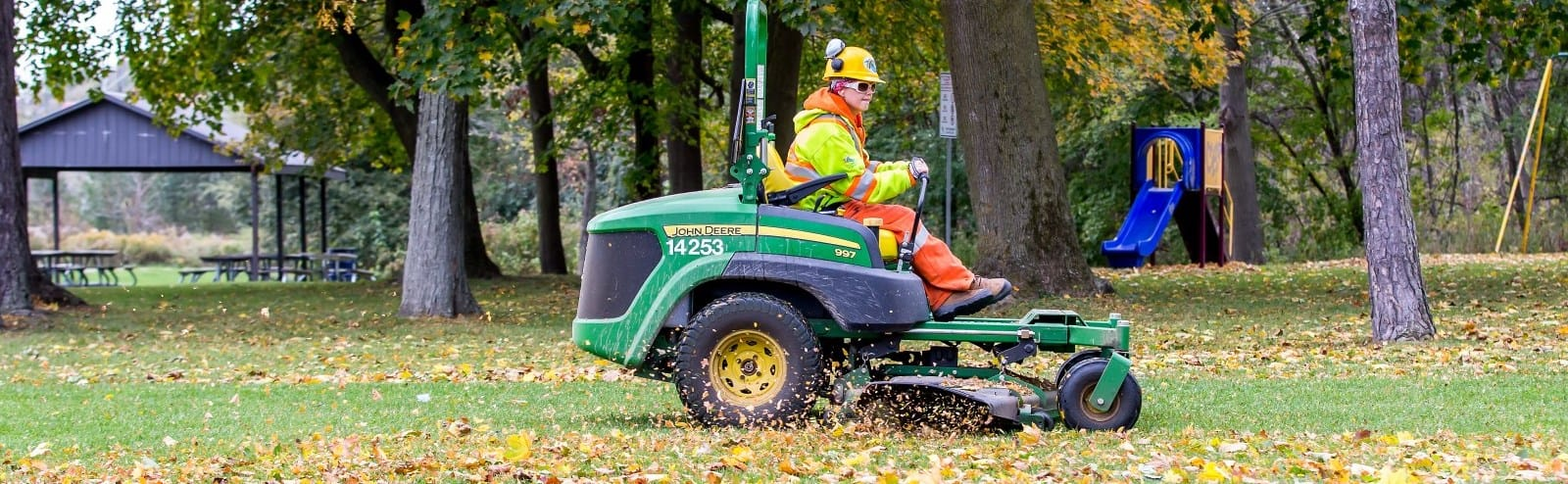 City worker on riding lawnmower.